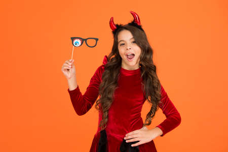 Foto de kid with party accessory. child celebrate autumn holiday. teenage girl in devil horns celebrate halloween. happy halloween. trick or treat concept. carnival festive costume of witch. Monster of Sale - Imagen libre de derechos