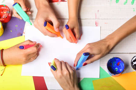 Photo pour Hands hold colorful markers and draw, top view - image libre de droit