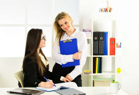 Photo pour colleagues engaged in brainstorming talk chatting. explain ideas at workplace. business colleagues in modern office. coach speaking to assistant. women discuss work issues. Busy working day at work - image libre de droit