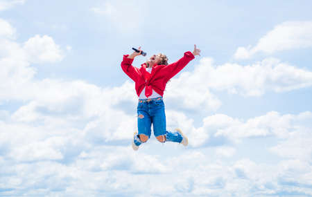 Photo pour Happy kid with microphone. karaoke concept. Singing Songs. Lifestyle and People Concept. make your voice louder. teen girl singing song with microphone. having a party. jump so high - image libre de droit