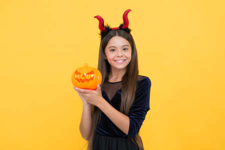 Foto de cute face. funny teen girl ready to celebrate party. costume party fun. happy halloween. child in imp horns with jack o lantern. kid wear devil horns hold pumpkin. childhood autumn holiday - Imagen libre de derechos