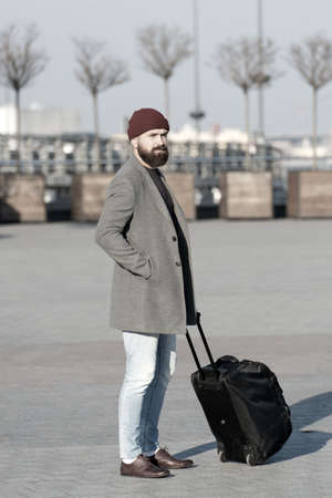 Photo for Man bearded hipster travel with big luggage bag on wheels. Let travel begin. Traveler with suitcase waiting transportation to airport railway station. Ready to travel. Carry travel bag. Business trip - Royalty Free Image