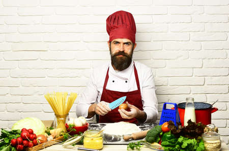 Photo pour Man with beard breaks egg with knife on white background - image libre de droit