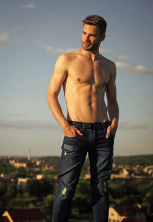 Photo for Hot day. Athletic handsome macho wear denim pants. Muscular body. Fitness model. Muscular bare torso. Six packs muscular chest. Man outdoors blue sky background. Summer trends. Male beauty concept - Royalty Free Image