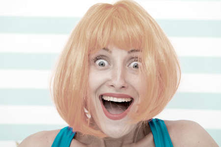 happy crazy girl with omg or wow facial expression. happy girl with crazy look. wow. surprised happy girl with orange hair. crazy look of girl saying omg. what a surprise. feeling and emotions