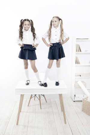 Photo for Primary school fashion. Happy school kids with fashion look standing on table. Fashion small girls with long hair ponytails smiling in class. Fashion for little students - Royalty Free Image