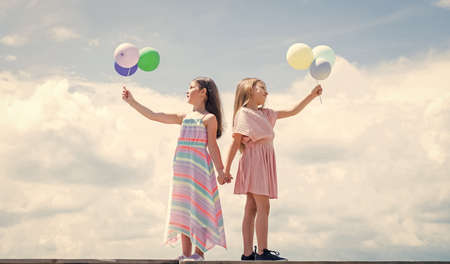 Photo pour summer vacation. small girls embrace. love and support. concept of sisterhood and friendship. family bonding time. best friends with balloon. two sisters hold party balloon. happy childhood - image libre de droit