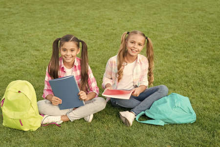Photo pour knowledge day came. having fun on green grass. two little kids with backpack. small girl play and study on school break. happy childrens day. sisterhood and family concept. Summer fun - image libre de droit