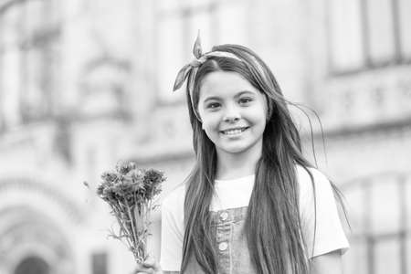 Shes cool, ooh girl. Happy girl hold flowers outdoors. Little girl with long hairstyle. Hair salon. Child girl with cute smile. Beauty look. Childhood and girlhood. Summer fashion and style