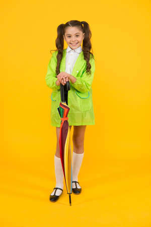 Childhood memories of playing in rain. Happy little child holding colorful umbrella on yellow background. Childhood activities on rainy autumn day. Childhood and school time. Enjoying happy childhood