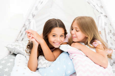 Photo pour Sisters share gossips having fun at home. Pajamas party for kids. Cozy place tipi house. Sisters or best friends spend time together lay in tipi house. Girls having fun tipi house. Girlish leisure - image libre de droit