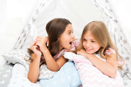 Photo pour Girlish leisure. Sisters share gossips having fun at home. Pajamas party for kids. Cozy place tipi house. Sisters or best friends spend time together lay in tipi house. Girls having fun tipi house - image libre de droit