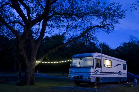 Foto de A large motorhome sits under a huge pecan tree, lit up as night falls on the campsite. - Imagen libre de derechos