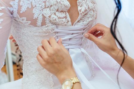 Foto de Morning bride. Bridesmaid helping the bride lacing up her dress - Imagen libre de derechos