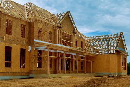Photo pour A new wooden house under construction in a blue sky - image libre de droit