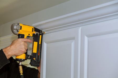 Photo pour Wood working using brad nail air gun to Crown Moulding on white kitchen cabinets framing trim, with the all power tools - image libre de droit
