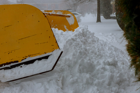 Excavator cleans the streets of large amounts of snow in city. Winter time concept.
