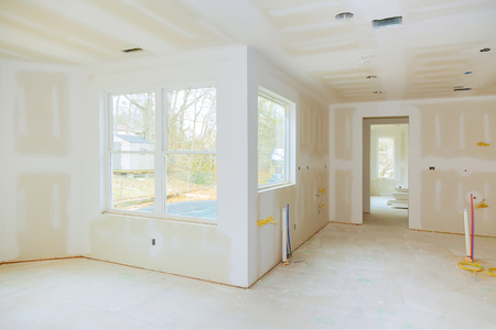 Photo for Interior construction of housing project with drywall installed and patched without painting applied interior with drywall installation and construction work in progress - Royalty Free Image