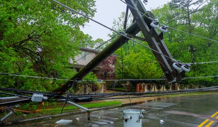 Photo pour The storm caused severe damage to electric poles power lines over a road after Hurricanepoles falling tilt. - image libre de droit