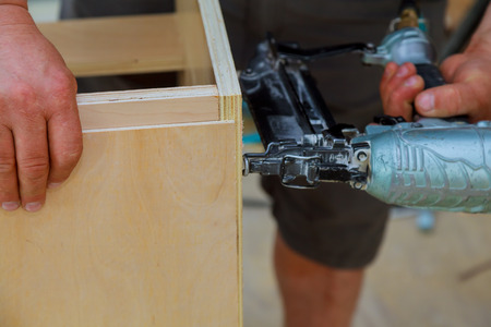 carpenter are shooting the nail by Air Nailer to wooding kitchen Home Improvement Kitchen Remodel worm