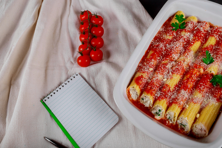 Italian pasta cannelloni with meat and tomato sauce, cheese on table