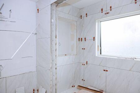 Foto de Work laying tile before applying tiles on bathroom tile. - Imagen libre de derechos
