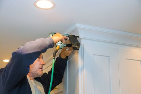 Photo pour Air nailer tool close up of carpenter using nail gun to crown moldings on kitchen cabinets with white cabinets - image libre de droit