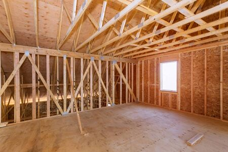 Photo pour Unfinished attic of a private house residential construction house framing agains - image libre de droit
