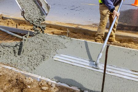 Photo for Construction worker pour cement for sidewalk in concrete works with mixer truck with wheelbarrow at construction site filling formwork with cement and gravel - Royalty Free Image