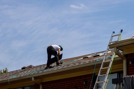 Photo pour Roof repair, worker with replacing gray tiles shingles on house being applied - image libre de droit