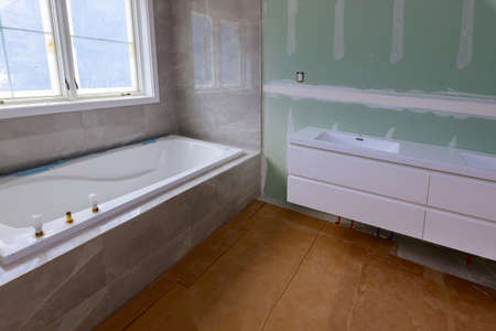 Photo pour Master Bathroom with new under construction bathroom interior drywall ready for tile in new luxury home - image libre de droit