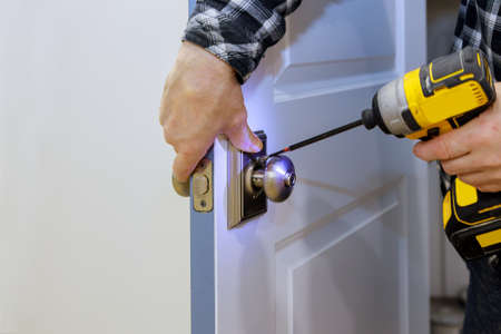 Photo for Master with screwdriver installs access the room door new lock in house. - Royalty Free Image