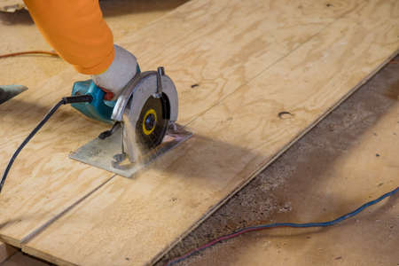 Photo for Man cutting plywood using an electrical chain saw professional tools - Royalty Free Image