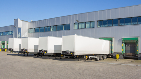 Foto de Trailers at docking stations of a distribution center waiting to be loaded - Imagen libre de derechos