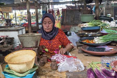 Surabaya, Indonesia - November, 05, 2017:  Woman cutting onions  at the market in Surabaya in Indonesia