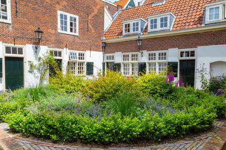 Photo for Courtyard with colroful garden and small houses in the center of city Leiden in the Netherlands, Europe - Royalty Free Image