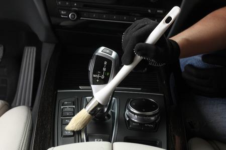 Foto de Car service: Worker Cleaning of interior by a soft brush. - Imagen libre de derechos