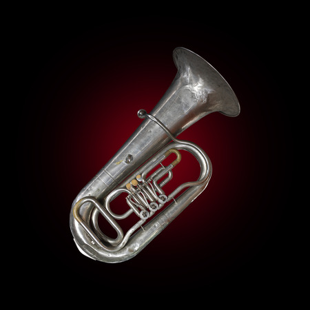 Musical brass instrument - Vintage tuba on a red and black background.
