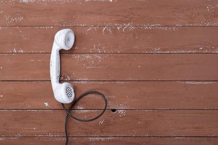 Photo pour White handset vintage phone on a retro old brown wood textured plank background - image libre de droit