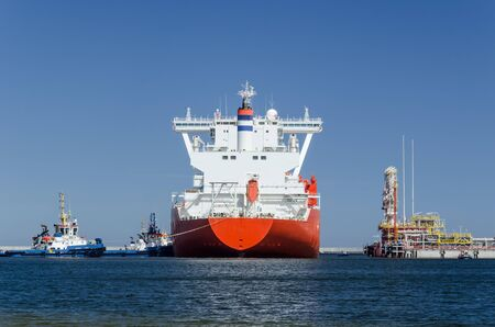 Photo pour GAS TANKER AND LNG TERMINAL - The big ship maneuvers in the mooring port at the wharf - image libre de droit