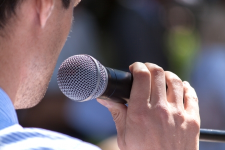 Speaker holds the microphone close up