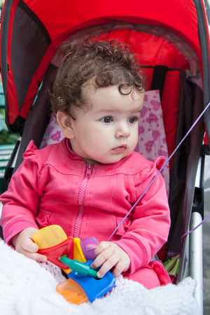 Portrait of baby girl sitting in stroller outdoors