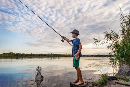 Photo pour Boy with a fishing rod catches fish standing on the bank of the river - image libre de droit