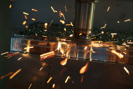 Photo pour The CNC milling machine rough cutting with the indexable tool. The sparking flame from the tool wear. - image libre de droit