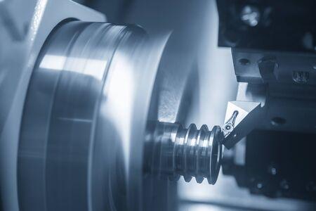 Photo pour The CNC lathe machine cutting the slot at the metal parts. The automotive parts manufacturing process by turning machine . - image libre de droit