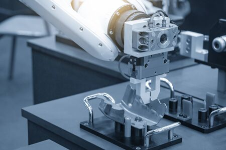 Photo pour The robotic arm gripping the formed sheet metal parts from the setting jig to the conveyor belt in automotive factory. The hi-technology  material handing process in by robotics system.  - image libre de droit