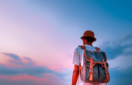 man with backpack and looking beautiful sky in sunset. concept for adventure and travel  in summer vacations and outdoor alonePhang Nga,Koh Yao Yai,Thailand;