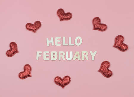 Photo pour Top view or flat lay of wooden letters HELLO FEBRUARY  with red glitter hearts on pink background. Greeting new month and Valentine's day. - image libre de droit