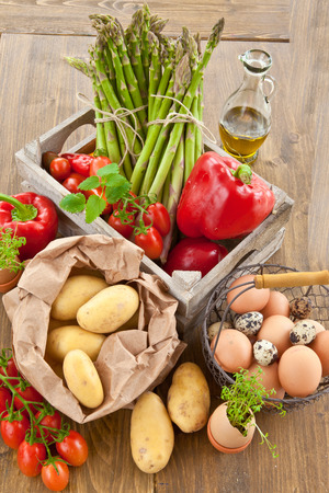 Fresh organic vegetables and eggs in wooden crate