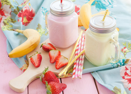 Photo for Vintage glass jars with milk and fresh strawberries and bananas - Royalty Free Image
